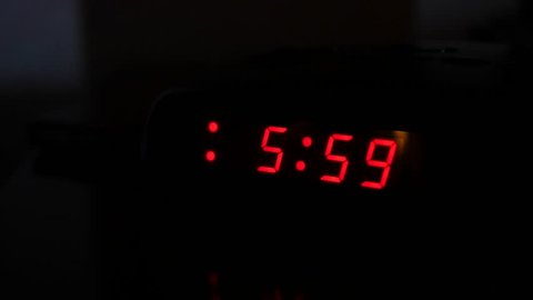 A man turns off the alarm when a digital alarm clock turns to six o'clock and turns on a light