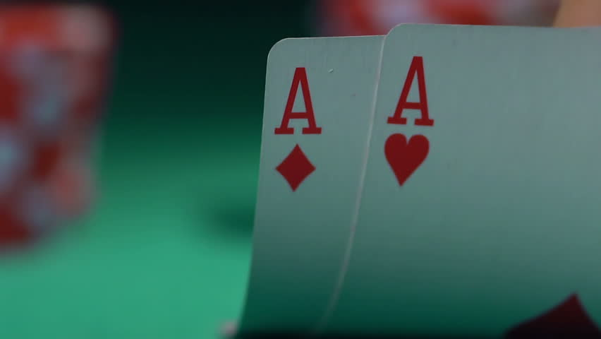 Extreme close-up of poker cards, player checking his hand before making bet. Casino customer playing at table, winning combination strategy, gambling fortune. Lucky tournament winner looking at pair