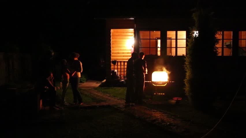 Resting unidentified people near house and brazier at summer night