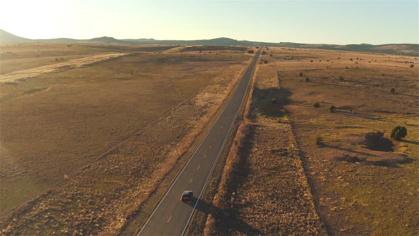 AERIAL: Flying above black SUV car driving along empty countryside road at sunset. People traveling, road trip through beautiful desert scenery in sunny summer | Shutterstock HD Video #16116070