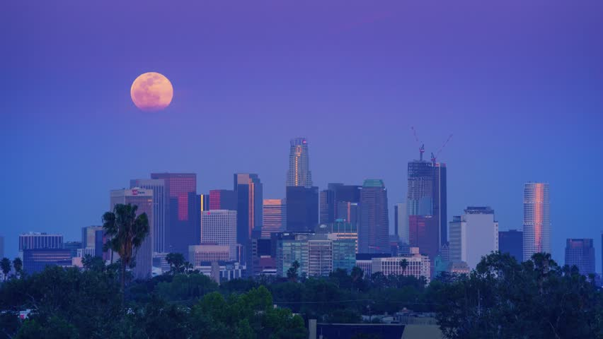 Full moon rising above downtown Los Angeles skyline during sunset to dusk to night transition. 4K UHD Timelapse