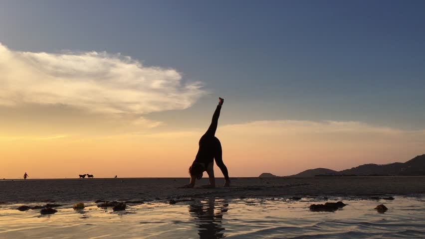 Silhouette woman with yoga posture on the beach at sunset | Shutterstock HD Video #16136596