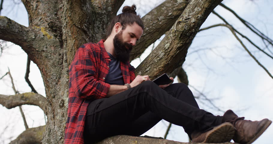 4k young carefree man sitting on a tree trunk away from hustle and bustle of a city and browsing the internet on a touchscreen tablet..   Shutterstock HD Video #16143130