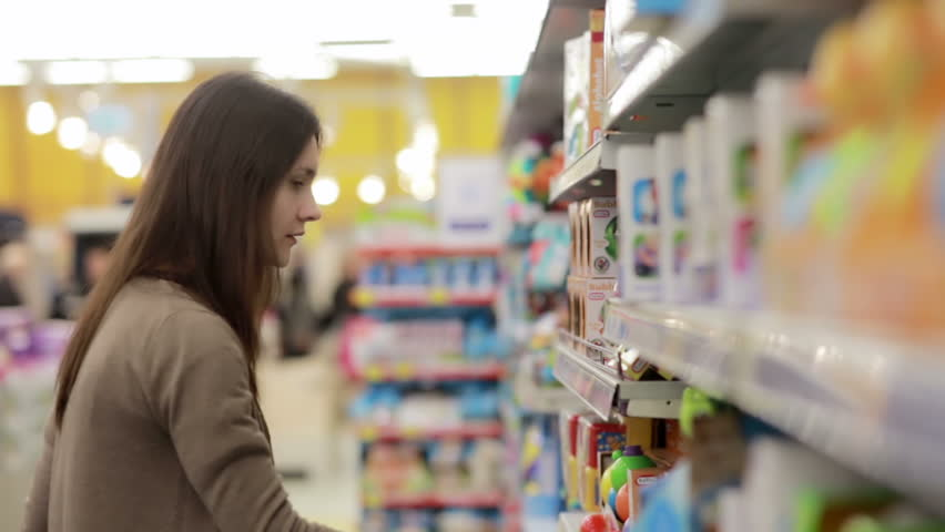 Young woman chooses baby toys in the supermarket | Shutterstock HD Video #16150192
