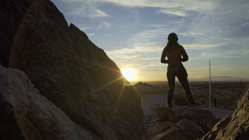 April 2016 - Los Angeles: One female looking at the sunset on the rocks in the desert | Shutterstock HD Video #16156429