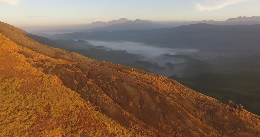 Aerial sunrise view over mountain with hikers and lush tea plantations in Munnar, India