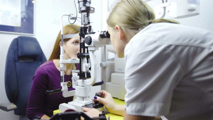Doctor checking eyes with biomicroscope device 4K. Dolly shot of female doctor examining eye structure with help of medical equipment. Professional health care.