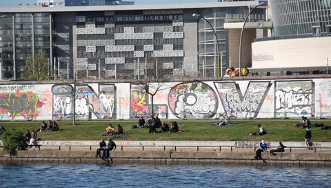 Berlin, Germany - april 21, 2016: People at remains of the Berlin Wall. The East side Gallery is a Berlin wall memorial, painted with graffiti from artist from all over the world.