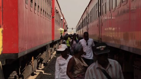 Luanda, Angola - circa 2011 - Medium shot between two stationary red coloured trains. Passengers descend from the trains and walk between the carriages towards the camera.