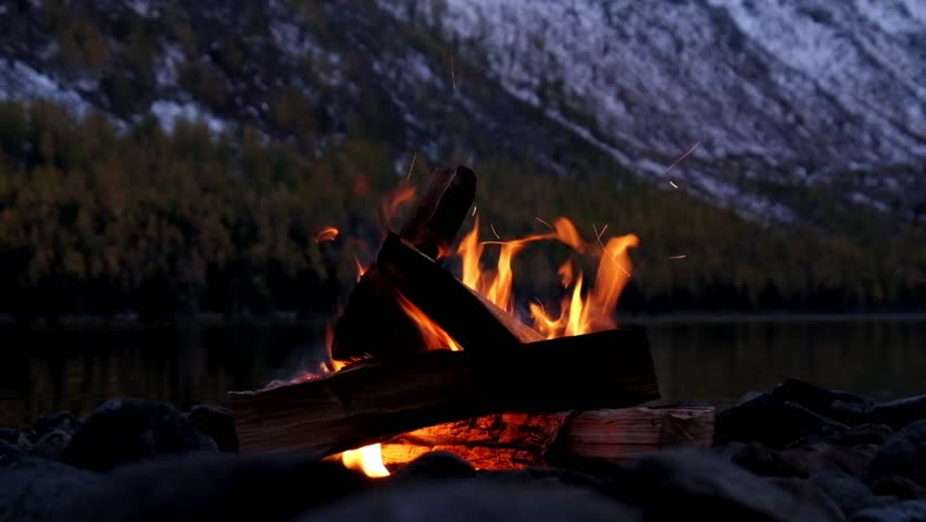 bonfire on the bank of Lower Multinskoe lake in the Altai Mountains at late evening with snow on mountains, Siberia, Russia
