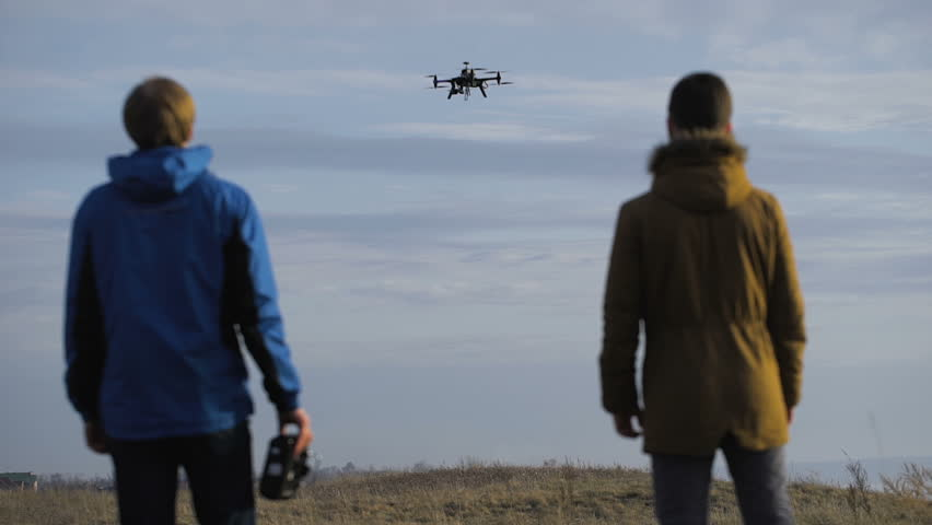 Two engineers watching the drone landing. Quadrocopters sits in automatic mode,