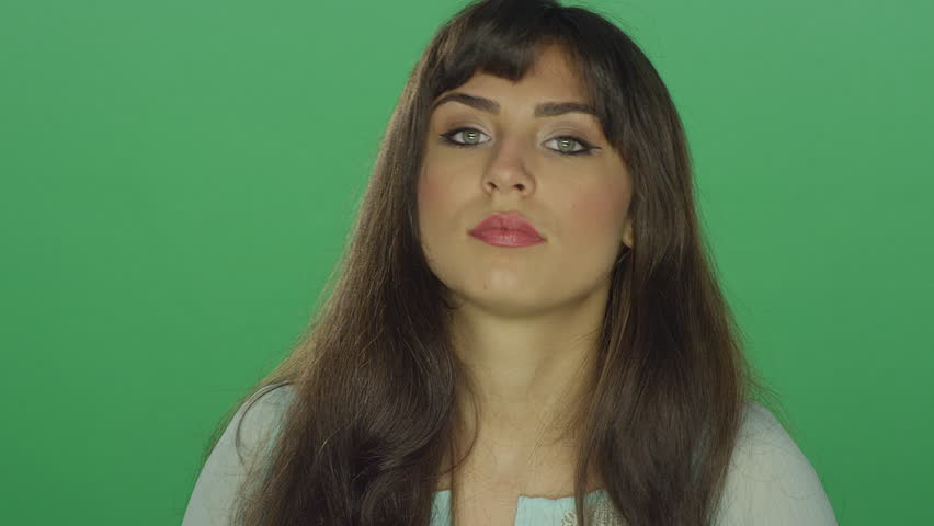 Beautiful brunette woman being shy and smiling, on a green screen studio background | Shutterstock HD Video #16252912