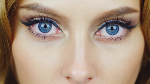 The eyes of a young woman looking into the camera. Expressive blue eyes
