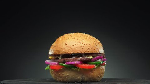 Fresh appetizing hamburger rotating on black background. Seamless loopable shot, 4k.