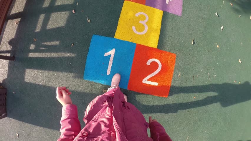 Girl jumps hopscotch on children playground, First Person View