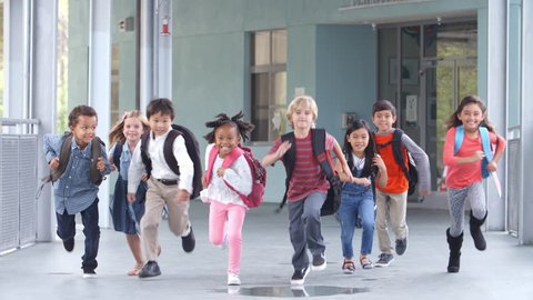 Group of elementary school kids running in a school corridor