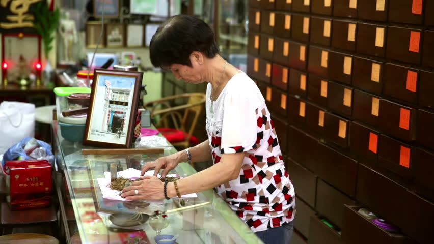 PENANG, MALAYSIA CIRCA APRIL 2016, Chinese traditional medicine shop, woman checking ingredients on paper wrapping with wooden cabinet of drawers behind | Shutterstock HD Video #16356142