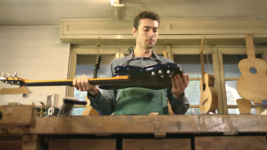 People and art, adult man at work as artisan in italian workshop with bass guitar and musical instruments, craftsman atelier