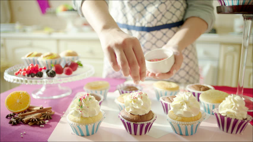 woman decorating cup cakes with sprinkling and berries shot of womans hands putting sprinkling