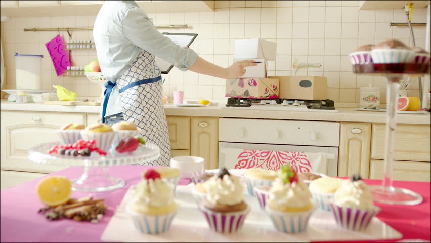 woman counting boxes in the kitchen shot of tasty cup cakes on the table