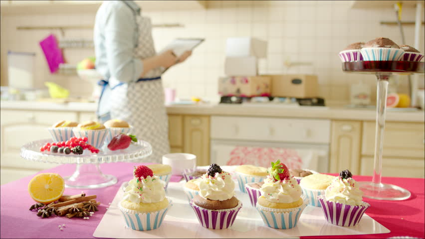 woman counting and registering boxes shot of tasty cup cakes on the table in