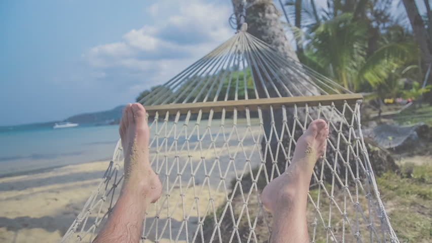 Swinging in a hammock, feets, POV. Relaxing on the beach with sea view