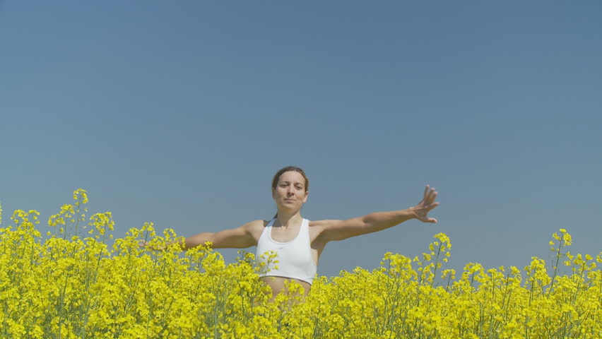happy woman pivoting in rape field