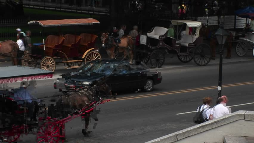 NEW ORLEANS - CIRCA 2009: Mule-drawn buggies wait for tourists, while another buggy makes its way down a crowded street in New Orleans.
