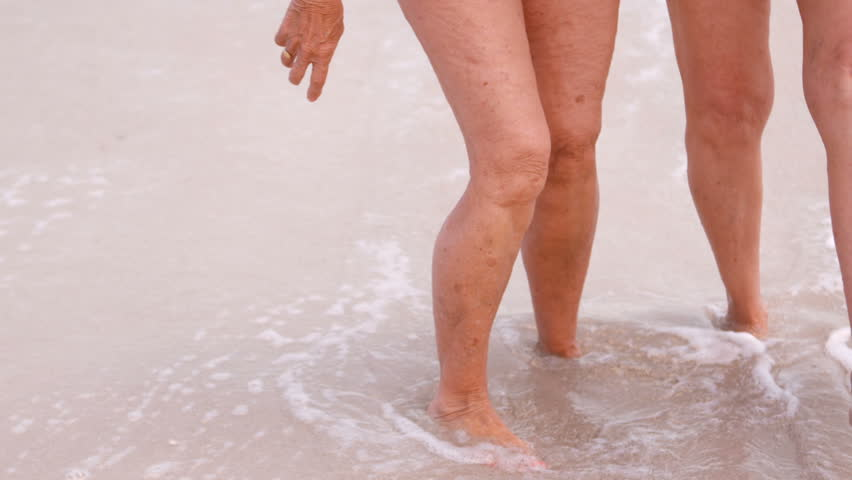 feet close-up. the girl goes to the sea at sunset. slow motion