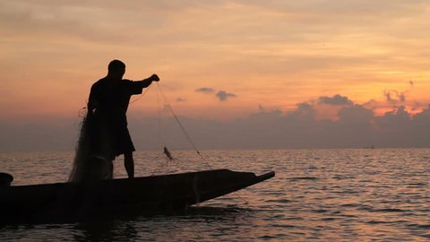 Silhouette of Fishermen fishing  in the lake at the sunrise time.