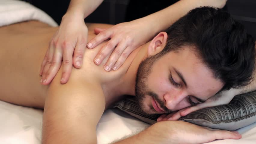 Close up locked down shot of young man having relaxing back massage in spa. Canon 7d mark11. Shutter speed 1/50. Aperture f4. Recording format H.264