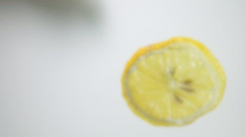 Round fresh lemon slice plunging into the transparent water  with explosive stunning splash, breaking the surface of liquid. Underwater high-speed slow motion shot on white background isolated. Camera