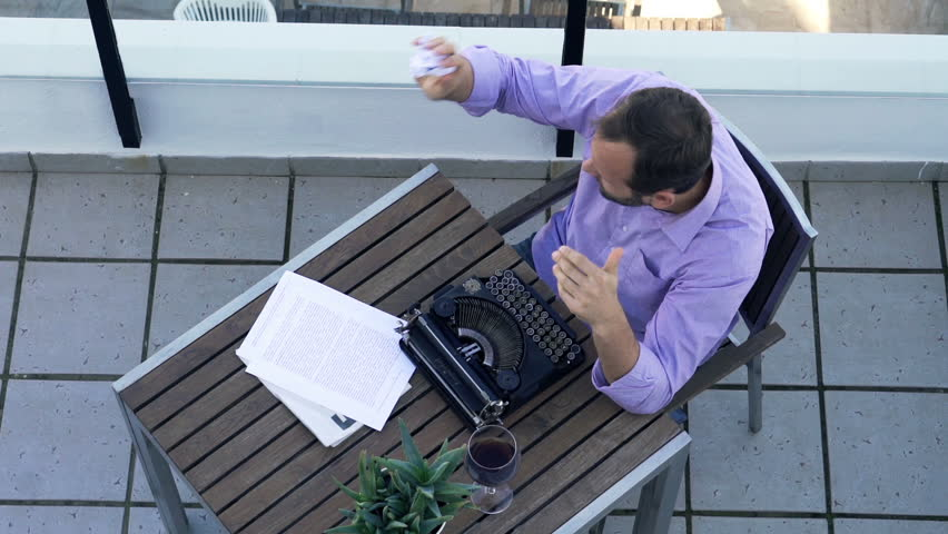 Angry male writer with typewriter throwing paper on terrace, top view  | Shutterstock HD Video #16556782