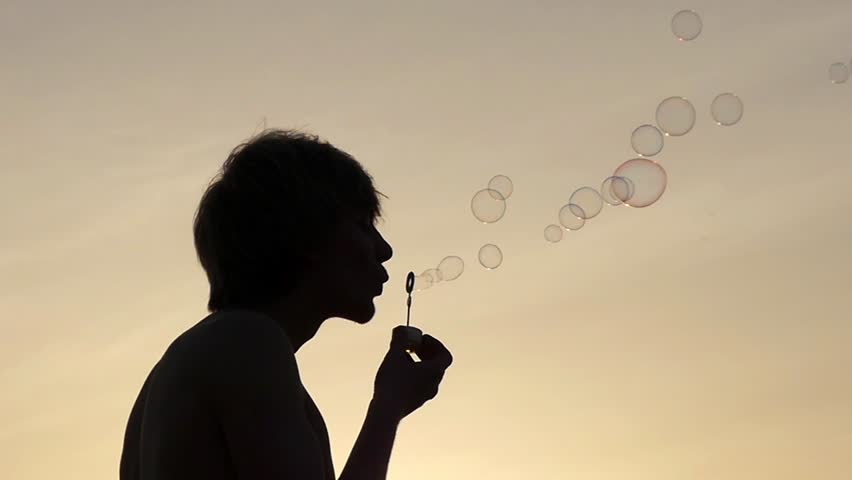 The Silhouette Of Guy Blow Bubbles At Sunset. Beautiful ...