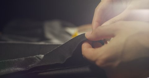 Slow motion of a hand of a young tailor who sews with a needle and thread by hand according to the ancient tradition