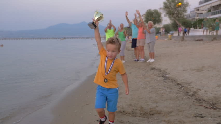 Steadicam slow motion shot of little boy with champion cup and medal, his family is applauding to him on the background.
