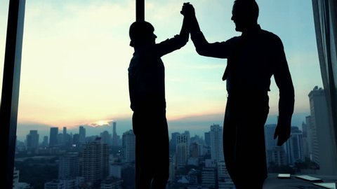 Successful business people giving high five in office, slow motion