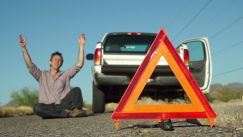Male in the distance dramatically lays down on the road with his broken down truck with hazard lights on parked on the side of the road and an emergency marker reflective triangle in the foreground.