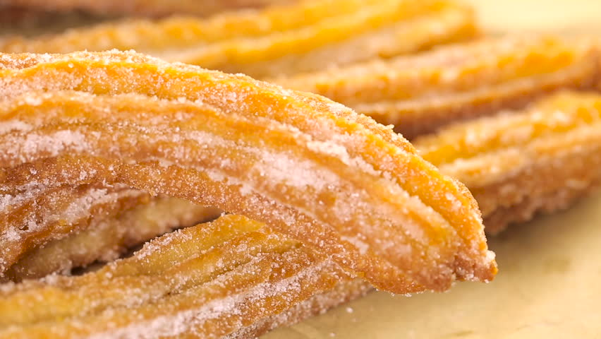 Bunch of churros covered with granulated sugar.
