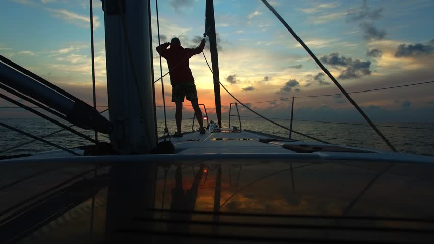 Young man standing with his back on the bow sailing yacht and looks forward in the course of the boat. Beautiful sunset sky in background. Look into the distance. Standing at deck of boat. | Shutterstock HD Video #16703404