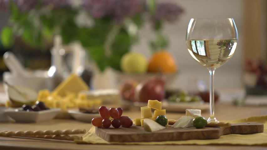 Hand taking the wooden board for cutting with cheese and grape. White wine on table. wine on table. white wine.