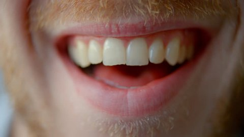 Extreme close up of a man's mouth changing shape as he smiles