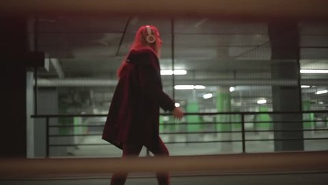 Teenage girl with long blonde hair walking fast along the street,listening to the music,wearing headphones at night under red lights, wearing black coat, jeans and high heel boots.