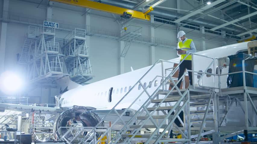 Aircraft Engineer in Safety Vest Walking Through Aircraft Maintenance Hangar. Shot on RED Cinema Camera in 4K (UHD).