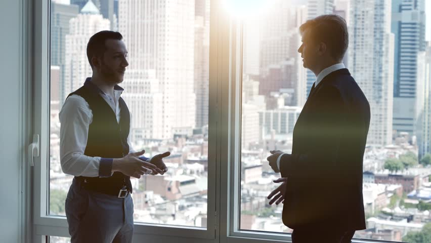 Two young businessman having a meeting in modern city office standing on window front. business people talking about financial profits growth concept  | Shutterstock HD Video #16832137
