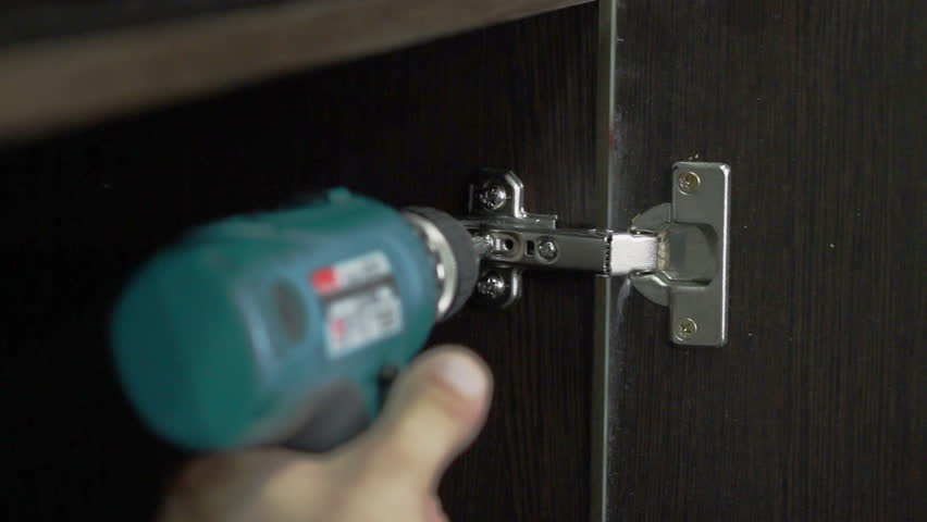 The worker is fastening the door hinge to the furniture detail using screwdriver #16864609