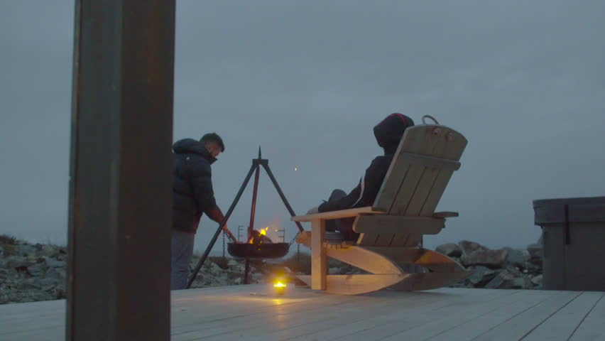 Man poking charcoal with stick. Young woman relaxing in a rocking chair. Tracking shot at twilight.
