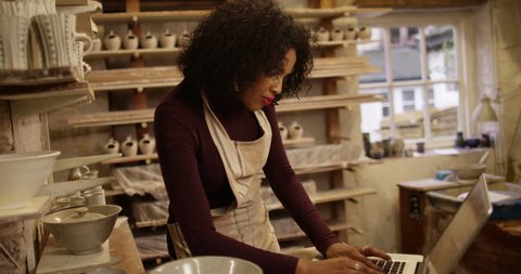 4K Small business owner in a pottery studio looking at laptop computer & checking sales