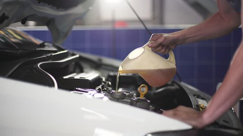 Auto mechanic is changing motor oil into a engine at car station