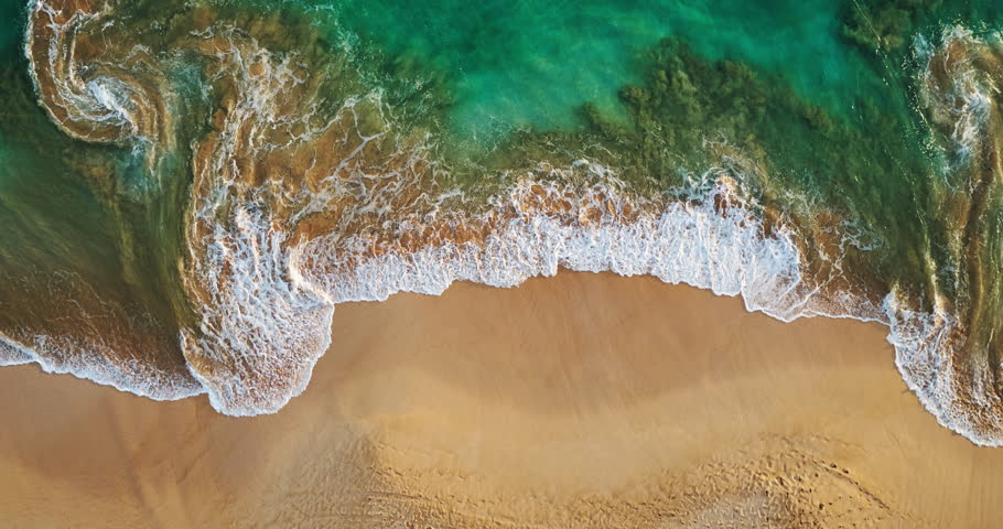 Aerial view waves break on white sand beach at sunset, land meets sea | Shutterstock HD Video #16911700